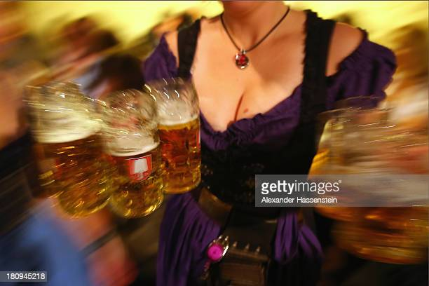 A waitress brings glasses of beer to the heads of the six Munich breweries meeting to taste their special Oktoberfest brews in the cellar of the...
