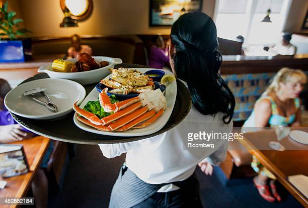 A waitress carries a tray a lobster kettle and a crab trio dish at a Red Lobster restaurant in Yonkers New York US on Thursday July 24 2014 Darden...