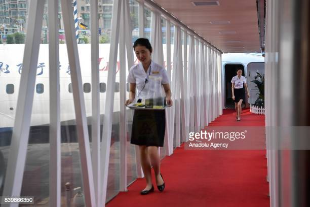 A waitress carries a tray at a restaurant converted from a Boeing 737 at Guanggu Walking Street in Wuhan of Hubei Province China on August 27 2017...