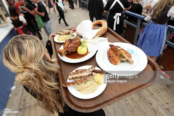 A waitress carries a tray with different bavarian dishes inside the Schottenhamel beer tent during day 2 of the Oktoberfest at Theresienwiese on...
