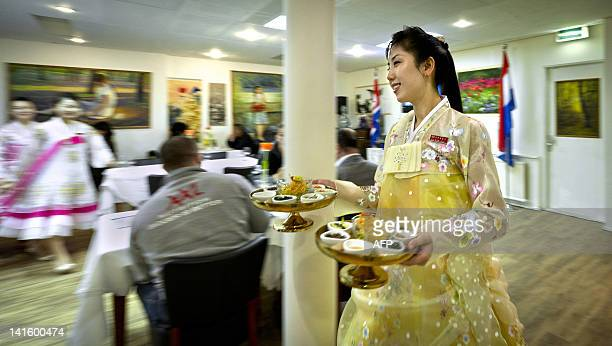 A waitress carries appetizers on March 10 2012 at Pyongyang the first NorthKorean restaurant in Europe in Amsterdam Taking its name from the isolated...