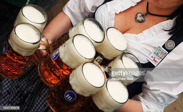 A waitress carries beer mugs as she wears a 'No Smoking' sign during the opening day of the Oktoberfest at Theresienwiese on September 18 2010 in...