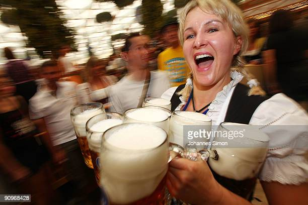 A waitress carries beer mugs at the Hofbraeuhausbeer tent on September 19 2009 in Munich Germany Oktoberfest is Germany's and the world largest fair...