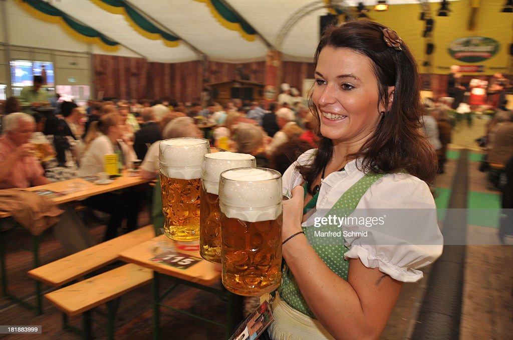 A waitress carries beer mugs during the 'Wiener Wirten Tag' as part of Wiener Wiesn Festival 2013 on September 25, 2013 in Vienna, Austria.