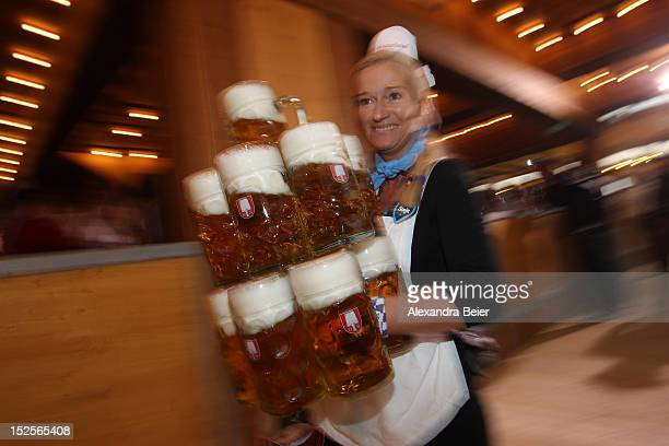 A waitress carries eleven beer mugs at a beer tent during the opening day of the Oktoberfest 2012 beer festival at Theresienwiese on September 22...
