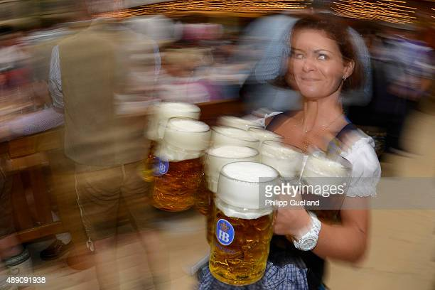 A waitress carries steins of beer at the Hofbraeu tent on the opening day of the 2015 Oktoberfest on September 19 2015 in Munich Germany The 182nd...