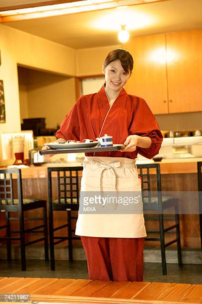 Waitress carrying a tray of sushi