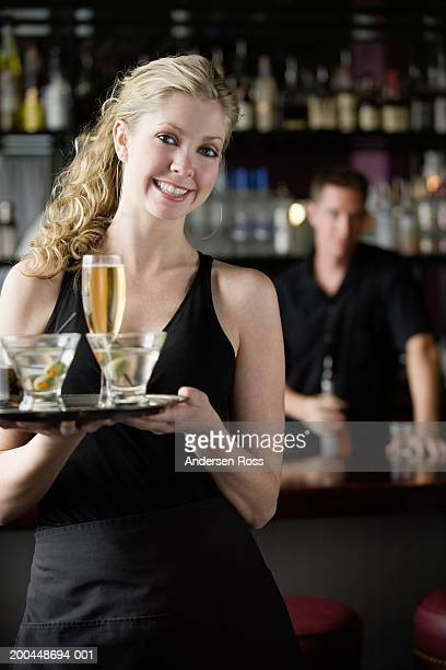 Waitress carrying tray of drinks, male bartender in background