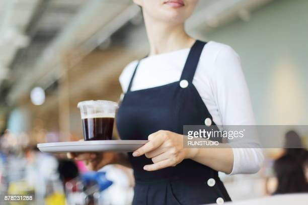 Waitress carrying tray with coffee