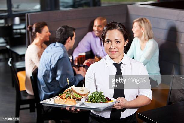 Waitress carrying tray with food