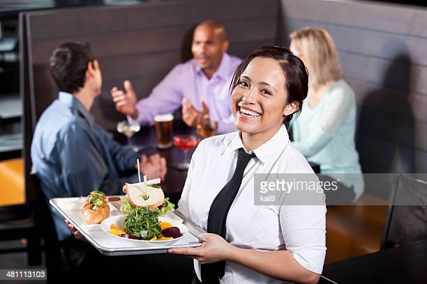 Camarera llevando una bandeja con alimentos