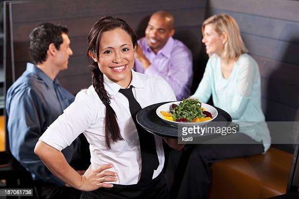 Serveuse transportant plateau avec salade