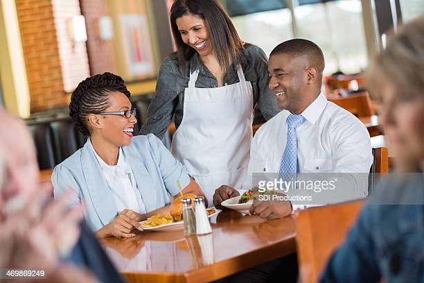 Waitress checking on couple during lunch in casual dining restaurant