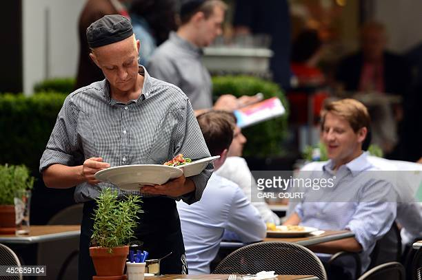 A waitress clears a table at a restaurant in central London on July 25 2014 Britain's economy grew strongly in the second quarter overtaking the size...