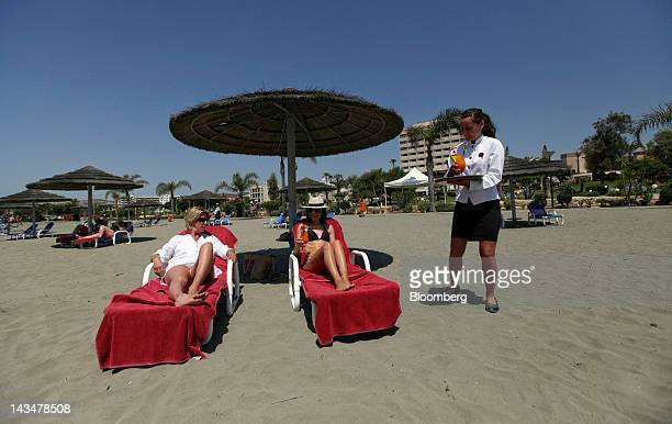 A waitress delivers drinks to guests as they sunbathe on the private beach at the St Raphael in Limassol Cyprus on Wednesday April 25 2012 Cyprus's...