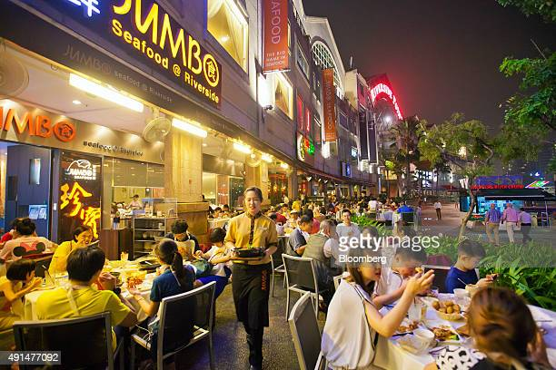 A waitress delivers food at the Jumbo Seafood Riverside restaurant operated by Jumbo Group at Clark Quay in Singapore on Monday Oct 6 2015 Jumbo...