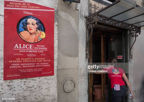 A waitress enters 'Pensao Amor' wearing a Tshirt that echoes the poster announcing Alice in Brothel Land on July 14 2017 in Lisbon Portugal 'Pensao...