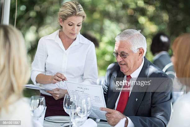 Waitress explaining menu to clients at table