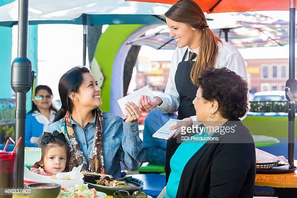 Waitress giving check to customer on patio at Tex-Mex restaurant
