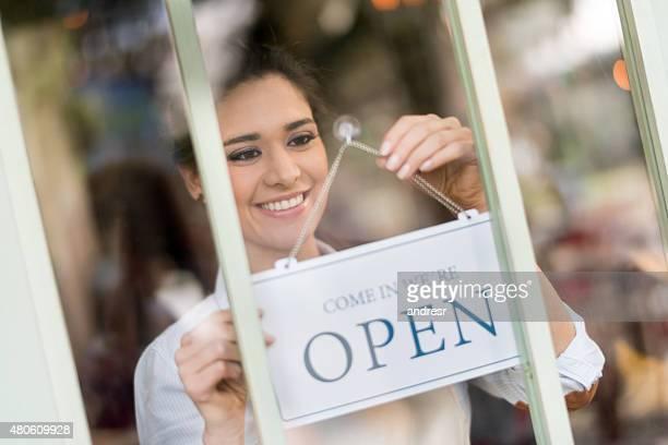 Waitress hanging an open sign at a restaurant