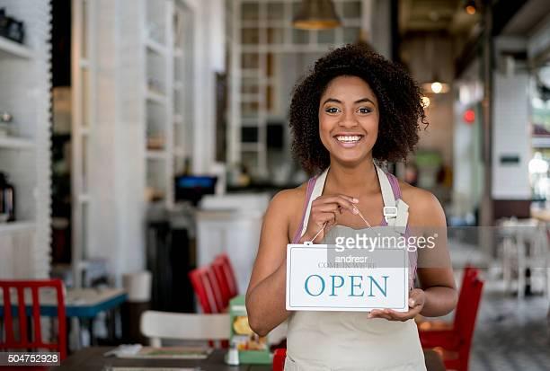 Waitress holding an open sign at a restaurant