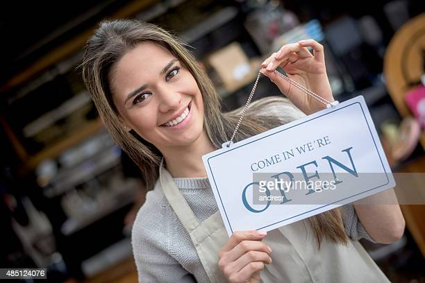 Waitress holding an open sign