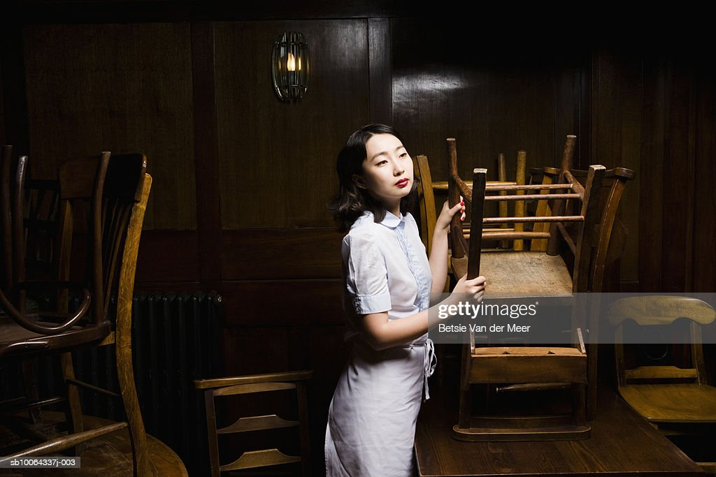 Waitress holding chair in restaurant, looking away : Stock Photo