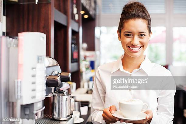 Serveuse tenant une tasse de café au Restaurant