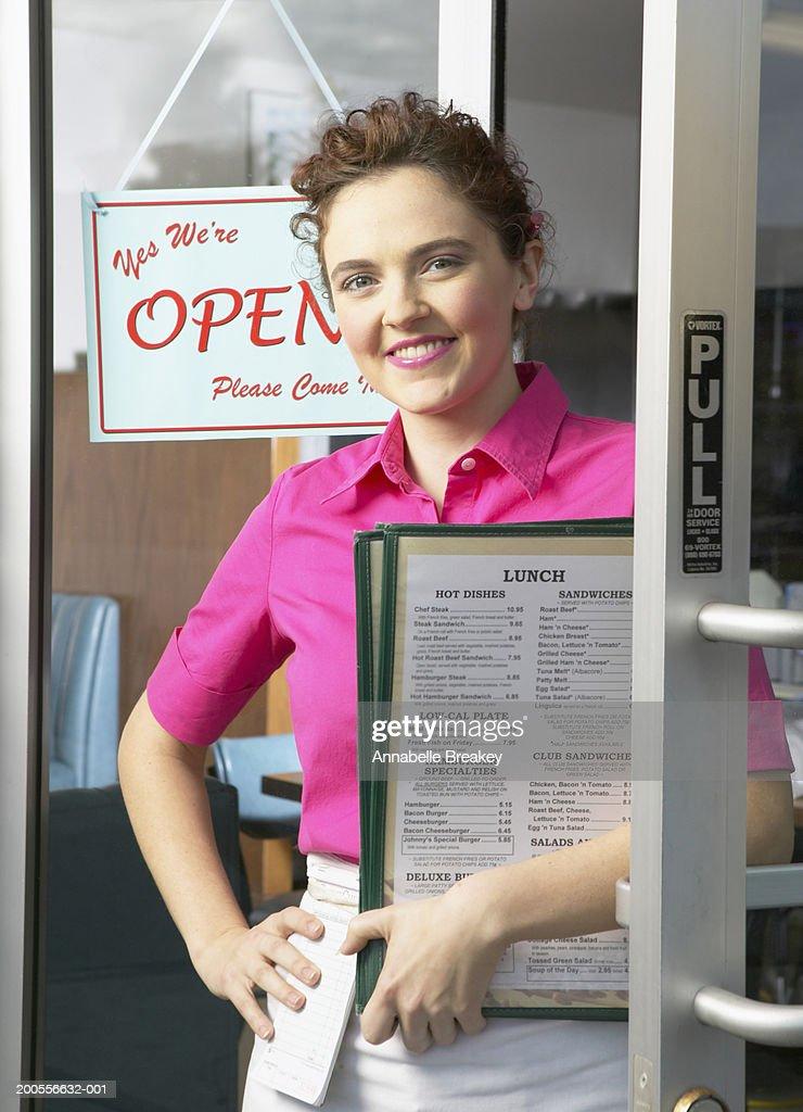 Waitress holding menus standing in doorway, smiling, portrait : Stock Photo