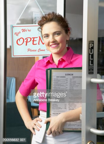 Waitress holding menus standing in doorway, smiling, portrait : Stock Photo
