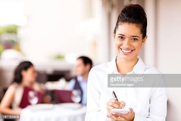 Serveuse tenir commande-notes et stylo avec Couple en arrière-plan