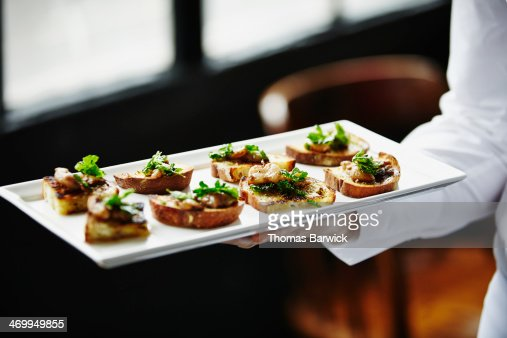 Waitress holding platter of organic appetizers