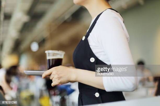 Waitress holding serving tray in cafe