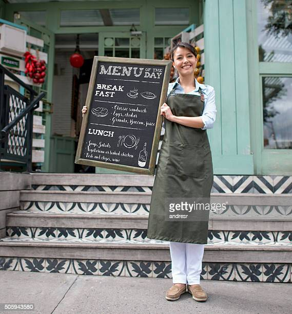 Waitress holding the menu of the day at a restaurant