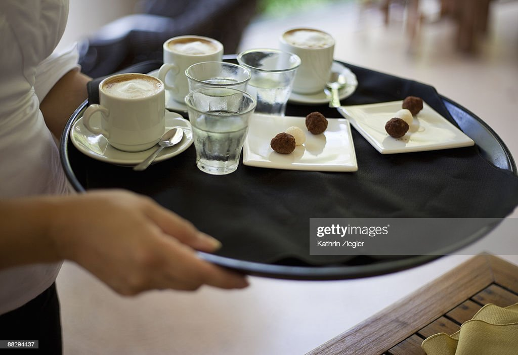 waitress holding tray with coffee and sweets : Stock Photo