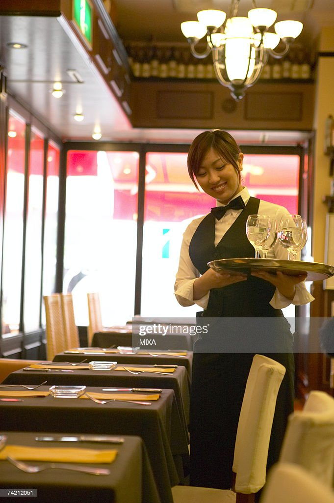 Waitress holding tray with glasses of water : Stock Photo