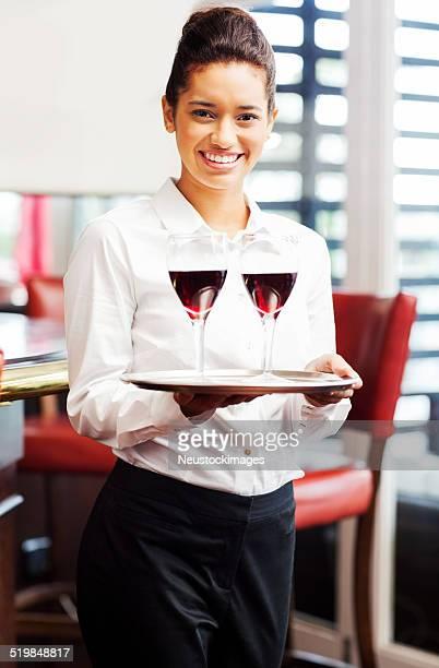 Kellnerin halten Tablett mit roten Wein Gläser im Restaurant