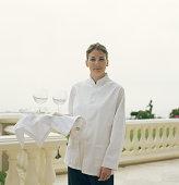 Camarera sosteniendo una bandeja con copas de vino, de retratos