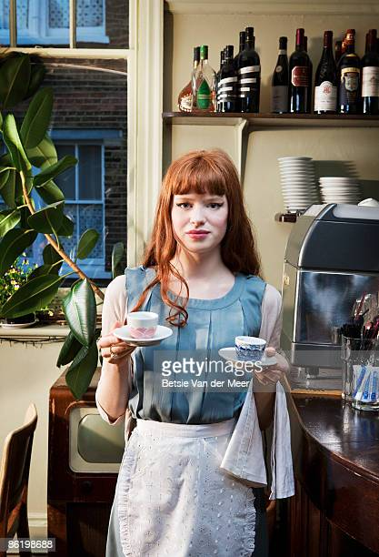 Waitress holding up coffeecups standing in cafe.