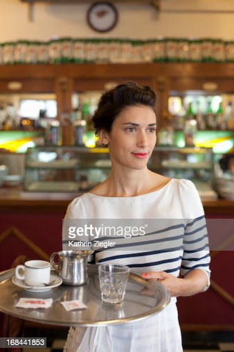 waitress in a beautiful café, holding tray : Stock Photo