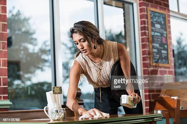 ウェイトレスのレストランのテーブル、布のクリーニング