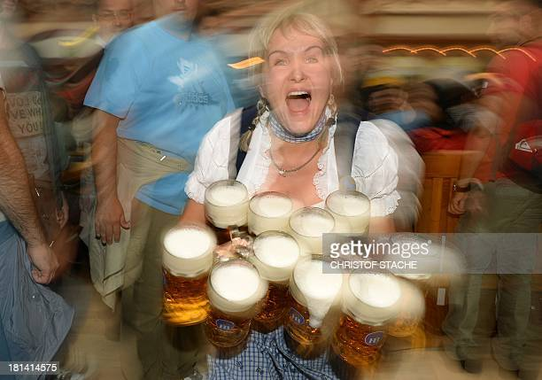 A waitress in a traditional Bavarian dirndl serves several beer mugs during the opening of the Oktoberfest beer festival at the Theresienwiese in...
