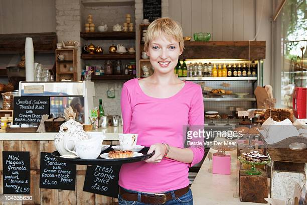 waitress in cafe holding tray with tea and cake.