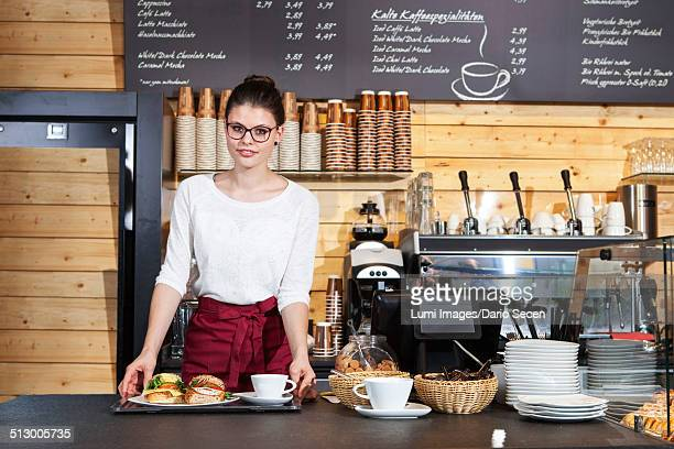 Waitress in coffee shop serving sandwiches on a tray