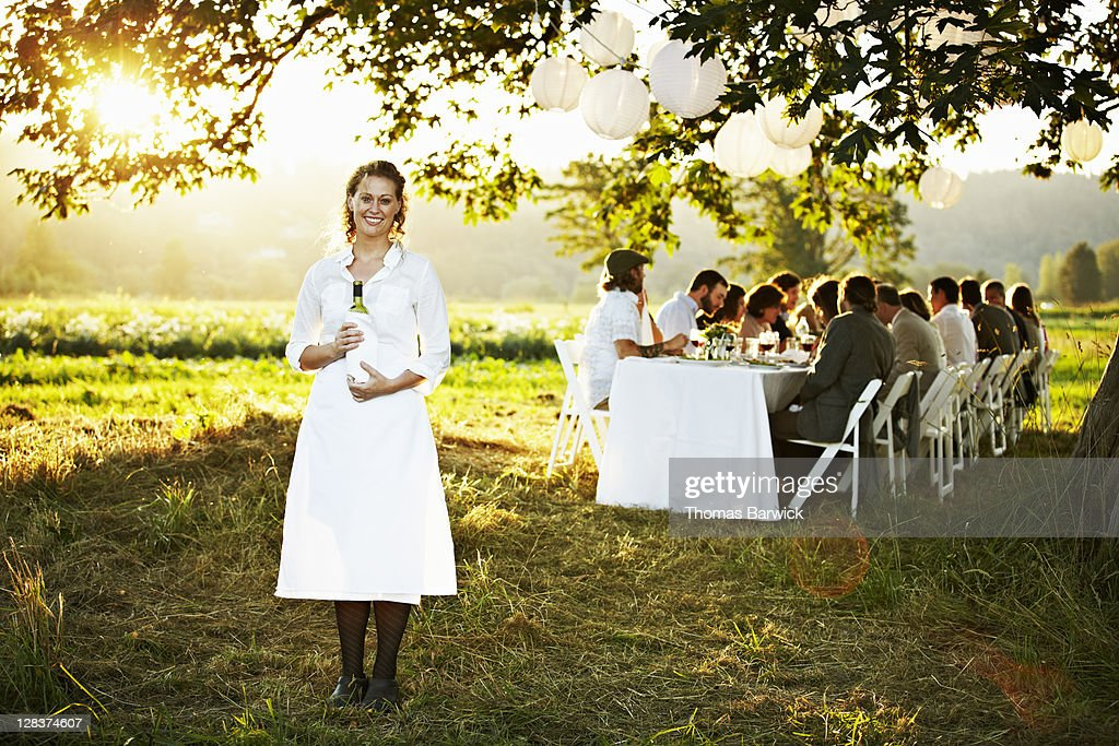 Waitress in front of outdoor banquet table : Stock Photo