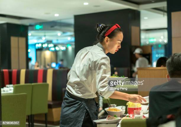 A waitress is serving the customers at a Haidilao restaurant Haidilao is China's most famous hotpot catering brand known its delicate service and...
