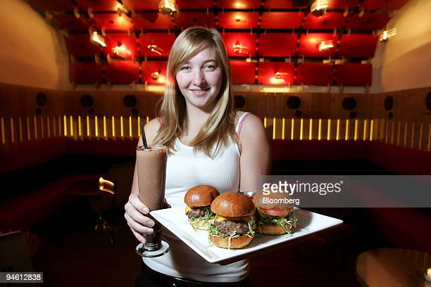 Waitress Jenny Guest poses with a plate of burgers and a chocolate milkshake in the second floor lounge of Pop Burger a restaurant located at 14 East...