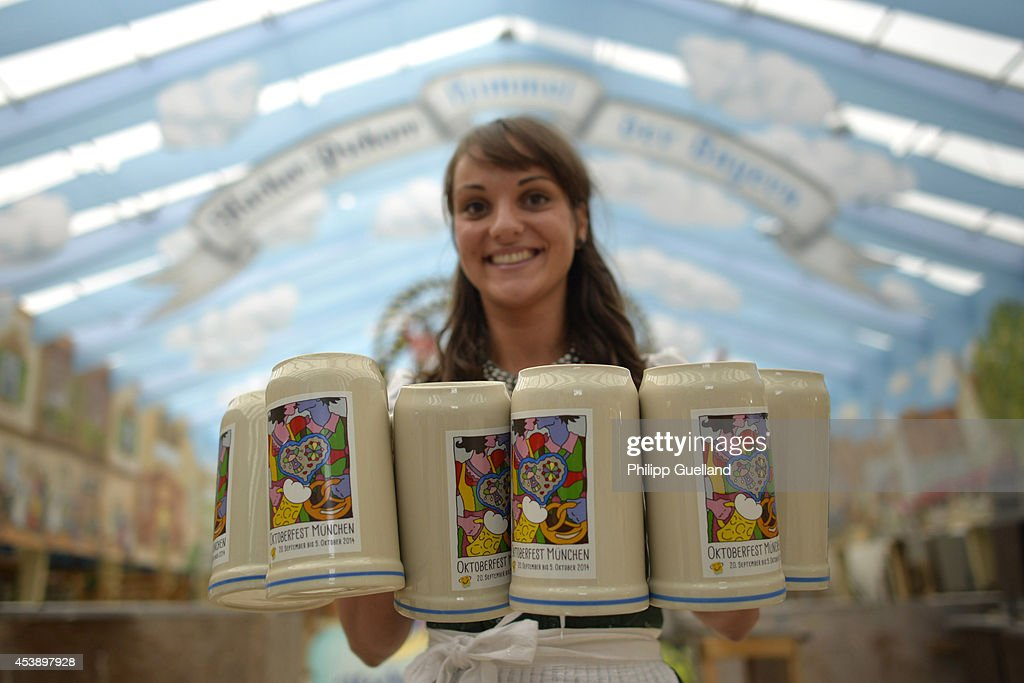 Waitress Julia presents the official 2014 Oktoberfest one-liter beer stein four weeks ahead of Oktoberfest on August 21, 2014 in Munich, Germany. Munich Oktoberfest, which opens to the public on September 20, draws millions of visitors and is the biggest beer fest in the world. Photo by Philipp Guelland/Getty Images)