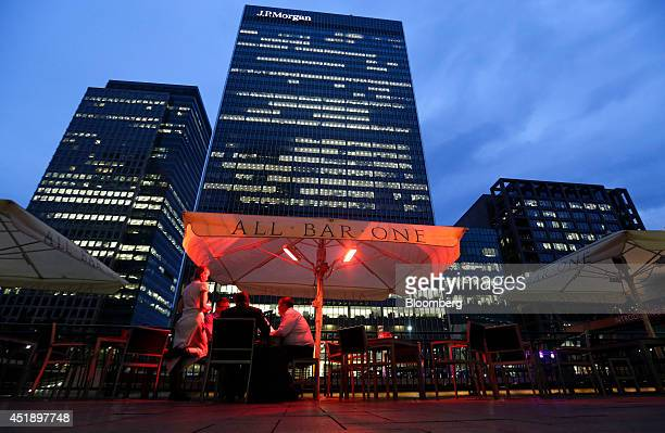 A waitress left serves customers as they sit outside an All Bar One bar operated by Mitchells Butlers Plc near the offices of JPMorgan Chase Co in...