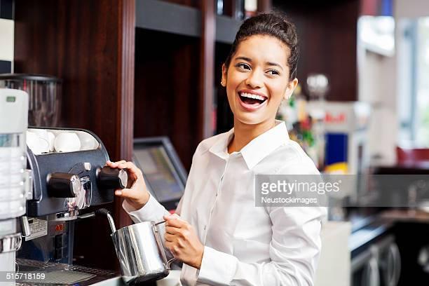 Kellnerin Wegsehen während seiner Kaffeemaschine im Restaurant
